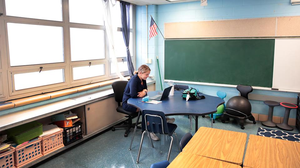 Lucy Baldwin, a teacher at King Elementary School, sits in an empty classroom teaching her students remotely during the first day of classes on September 08, 2020 in Chicago, Illinois. (Scott Olson/Getty Images)