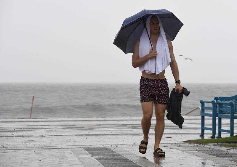 A pedestrian holds an umbrella during heavy rain in Coogee, Sydney.
