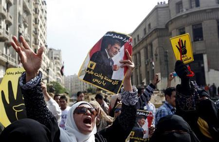 Supporters of ousted Egyptian president Mohamed Mursi hold his posters outside Egyptian High Court in Cairo