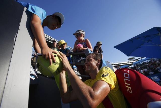Vasek Pospisil of Canada signs autographs for fans after defeating Samuel Groth of Australia in their men's singles match at the Australian Open 2014 tennis tournament in Melbourne January 13, 2014. REUTERS/Bobby Yip (AUSTRALIA - Tags: SPORT TENNIS)