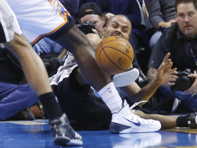 San Antonio Spurs guard Tony Parker (9) passes off after falling down in the second quarter of an NBA basketball game against the Oklahoma City Thunder in Oklahoma City, Wednesday, Nov. 27, 2013. (AP Photo/Sue Ogrocki)