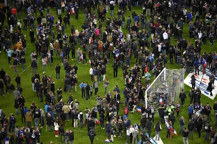 Football fans gather in the field as they wait for security clearance to leave the Stade de France on November 13, 2015 following shootings and explosions near the stadium and in other parts of Paris (AFP Photo/Franck Fife)