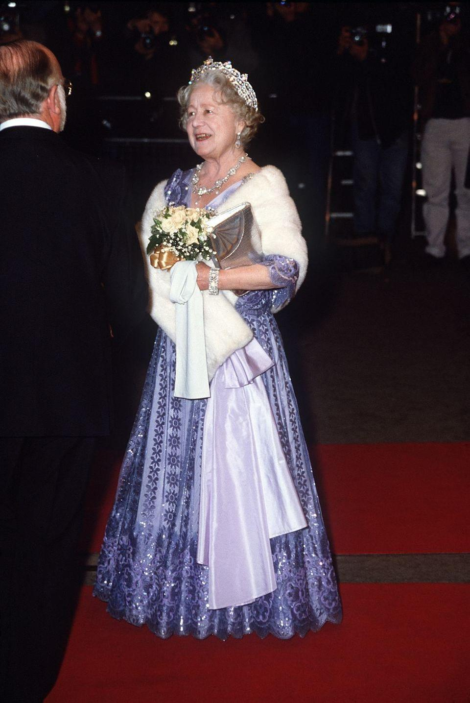 <p>The Queen Mother covered up in a white fur stole at a 1983 film premiere in London, however you can still see the glaring similarities to Rapunzel's purple gown. </p>