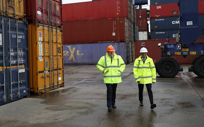 Boris Johnson and Rishi Sunak walk past shipping containers during a visit to Teesport in Middlesbrough - PA
