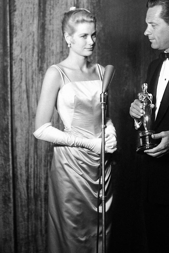"""<p><a href=""""https://www.instyle.com/celebrity/grace-kelly"""">Grace Kelly</a> won an Oscar for her performance in <em>The Country Girl</em> while wearing an ice-blue gown by Edith Head. The gown, which was originally created for the movie's premiere, was cut from a bolt of $4,000 French satin and paired with a matching evening coat, a red lip, and a perfectly glamorous updo.</p>"""