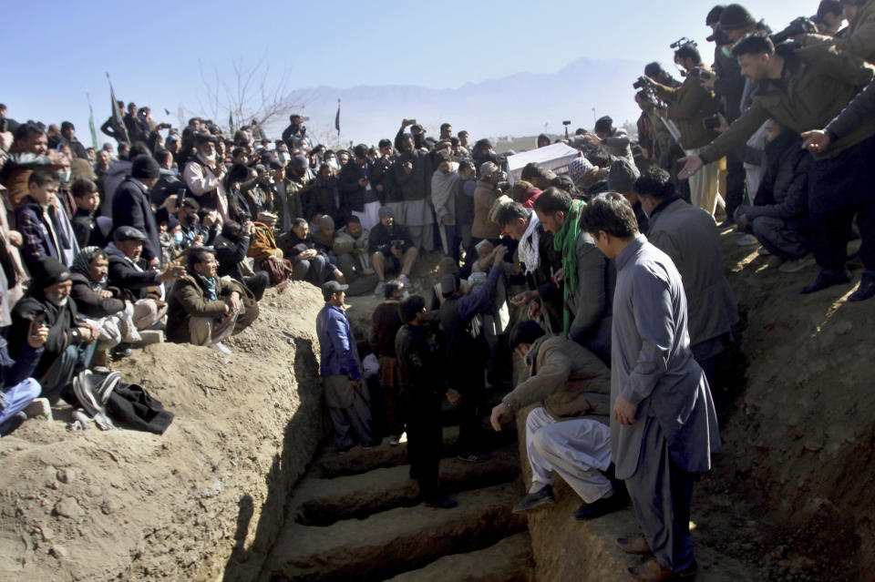People bury the coal mine workers who were killed by gunmen near the Machh coal field in Quetta, Pakistan, Saturday, Jan. 9, 2021. Hundreds of Pakistani Shiites gathered to bury 11 coal miners from the minority Hazara community who were killed by the Islamic State group, ending over a week of protests that sought to highlight the minority community's plight. (AP Photo/Arshad Butt)