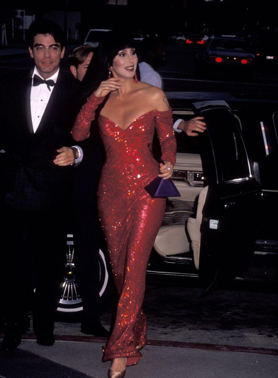 <p>Filming a scene for <em>The Player</em> with Peter Gallagher in a red sequin gown and tassel earrings. </p>