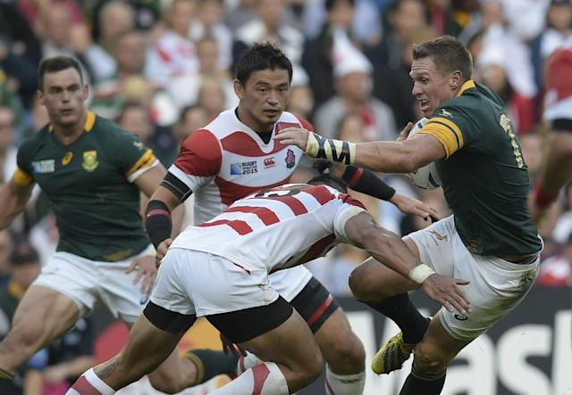 South Africa's captain and centre Jean de Villiers (R) is tackled by Japan's centre Male Sau (C) during Pool B match of 2015 Rugby World Cup at the Brighton community stadium, south east England on September 19, 2015 (AFP Photo/Lionel Bonaventure)