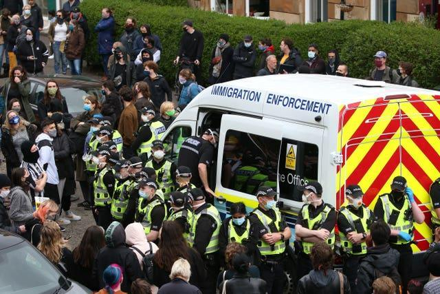 An immigration van in Kenmure Street, Glasgow, surrounded by protesters