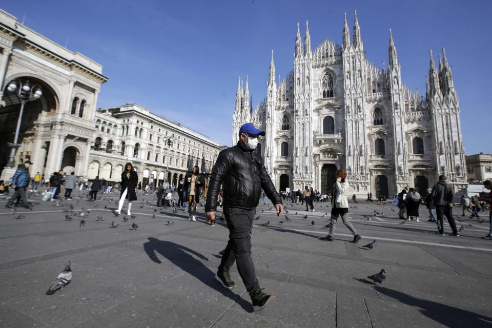 A man wearing a sanitary mask walks past the Duomo gothic cathedral in Milan, Italy, Monday, Feb. 24, 2020. Italy has been scrambling to check the spread of Europe's first major outbreak of the new viral disease amid rapidly rising numbers of infections and calling off the popular Venice Carnival, scrapping major league soccer matches in the stricken area and shuttering theaters, including Milan's legendary La Scala. (AP Photo/Luca Bruno)