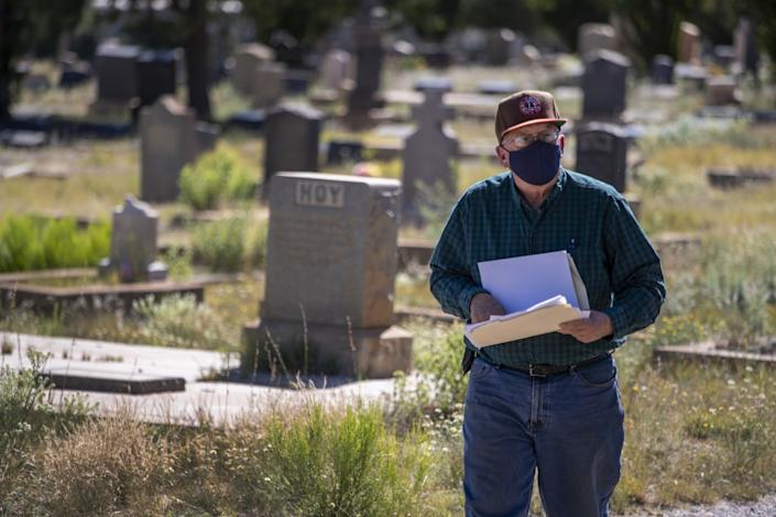 "Historian Mike Anderson looks for victims of the 1918 flu at Evergreen Cemetery. <span class=""copyright"">(Brian van der Brug / Los Angeles Times)</span>"
