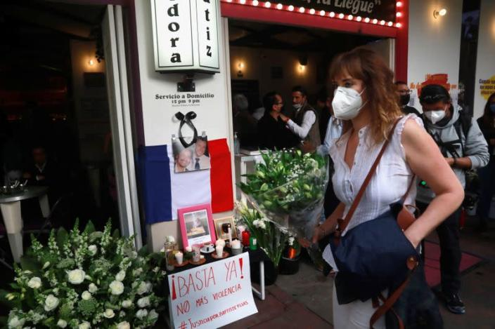 A member of the French community living in Mexico holds flowers past an altar outside a restaurant owned by French businessman Baptiste Jacques Daniel Lormand after he was found murdered, in Mexico City