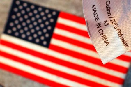 """The label reading """"Made in China"""" on a sweatshirt is seen over another shirt with a U.S. flag at a souvenir stand in Boston"""