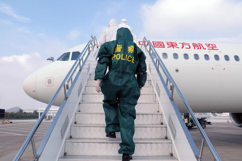 Chinese police officer and medical workers wearing protective clothing board a plane to check the body temperatures of the passengers onboard for prevention of the new coronavirus and pneumonia at Putuoshan Airport during the Chinese New Year or Spring Festival holiday in Zhoushan City, east China's Zhejiang Province on January 28th, 2020. (Photo by Zou Xunyong / Costfoto/Sipa USA)