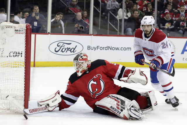 New Jersey Devils goaltender Cory Schneider, left, eyes the puck as Montreal Canadiens center Phillip Danault attacks during the third period of an NHL hockey game, Monday, Feb. 25, 2019, in Newark, N.J. The Devils won 2-1. (AP Photo/Julio Cortez)
