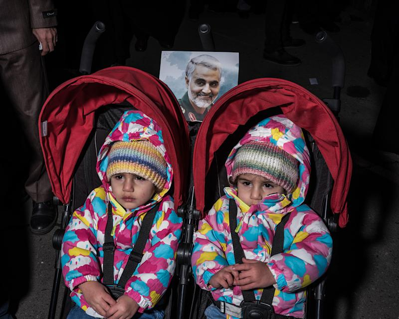 Two children are pushed in a double stroller through a crowd of mourners. | Newsha Tavakolian—Magnum Photos for TIME