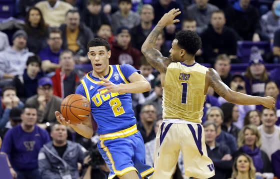 UCLA's Lonzo Ball (2) looks for room to pass around Washington's David Crisp in an NCAA college basketball game Saturday, Feb. 4, 2017, in Seattle.