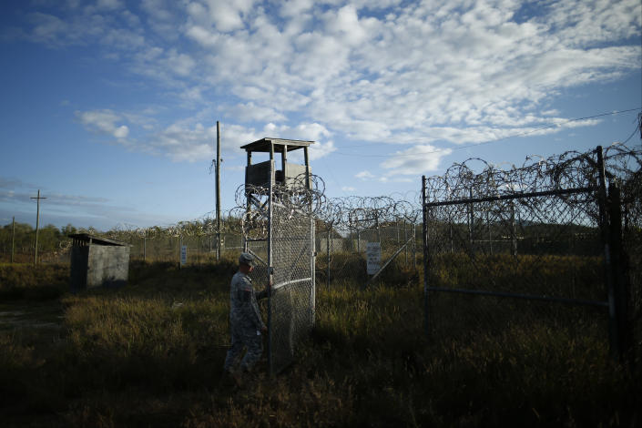 FILE - In this Nov. 21, 2013, file photo reviewed by the U.S. military, a soldier closes the gate at the now abandoned Camp X-Ray, which was used as the first detention facility for al-Qaida and Taliban militants who were captured after the Sept. 11 attacks at Guantanamo Bay Naval Base, Cuba. Detainees were housed in open air pens until the completion of Camp Delta in April 2002. Many detainees at Guantanamo Bay may be closer to heading home under a bipartisan deal reached in Congress that gives President Barack Obama a rare victory in his fight to close the prison for terror suspects. The White House says it intends to shutter the prison on the U.S. base in Cuba, which opened in January 2002 and where most of the 39 men still held have never been charged with a crime. (AP Photo/Charles Dharapak, File)