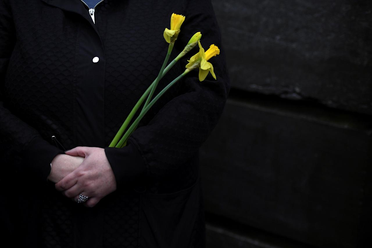 Schoolfriends bring yellow flowers to represent sunshine as they queue up to view Cranberries singer Dolores O'Riordan's coffin as it is carried into St. Joseph's Church for a public reposal in Limerick, Ireland January 21, 2017. REUTERS/Clodagh Kilcoyne     TPX IMAGES OF THE DAY