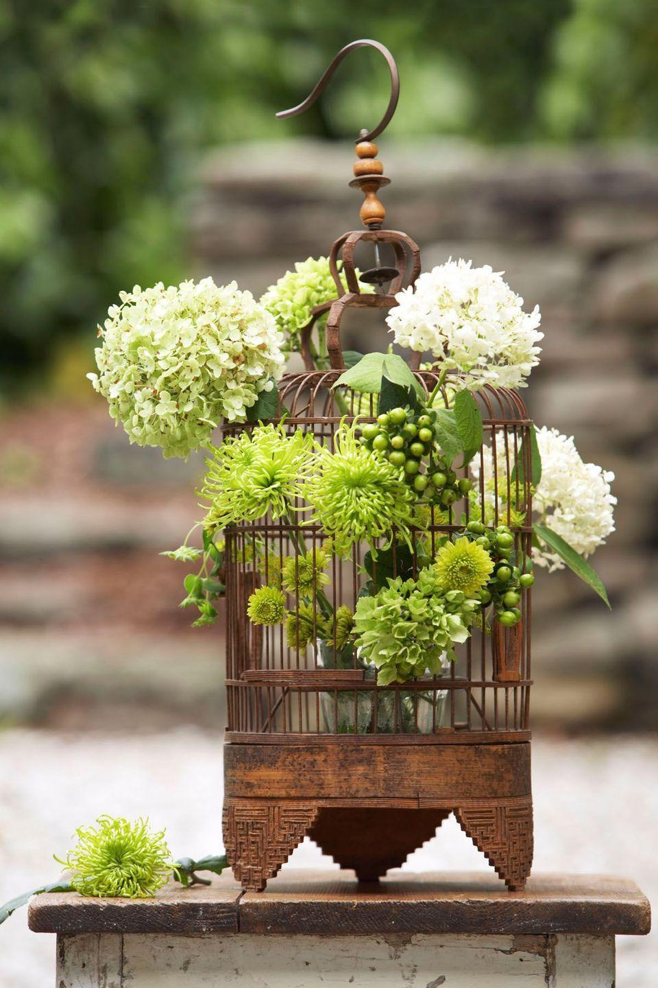 <p>A vintage-inspired birdcage makes an ideal display for top-heavy foliage like hydrangeas and hypericum berries. Find your own vintage aviary at a flea market or tag sale, remove its perch, and pop a small vase inside. Then slip a variety of blooms between the bars.</p>