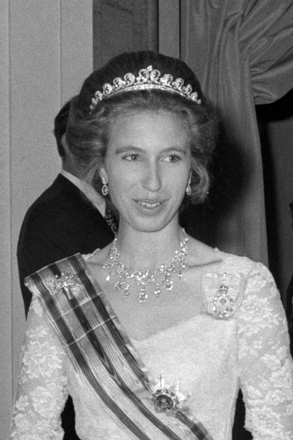 Princess Anne arrives at Claridge's for a banquet in 1969, stunning in a regal tiara and necklace, as well as a white gown, with a sash. (Getty Images)