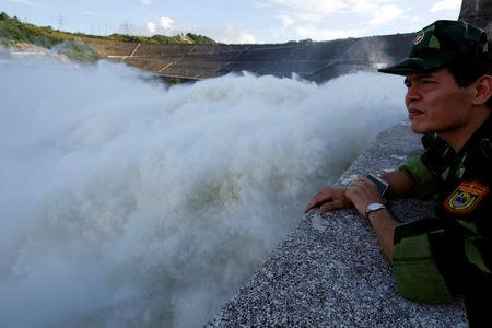 A soldier watches as Hoa Binh hydroelectric power plant opens the flood gates after a heavy rainfall caused by a tropical depression in Hoa Binh province, outside Hanoi, Vietnam October 12, 2017. REUTERS/Kham