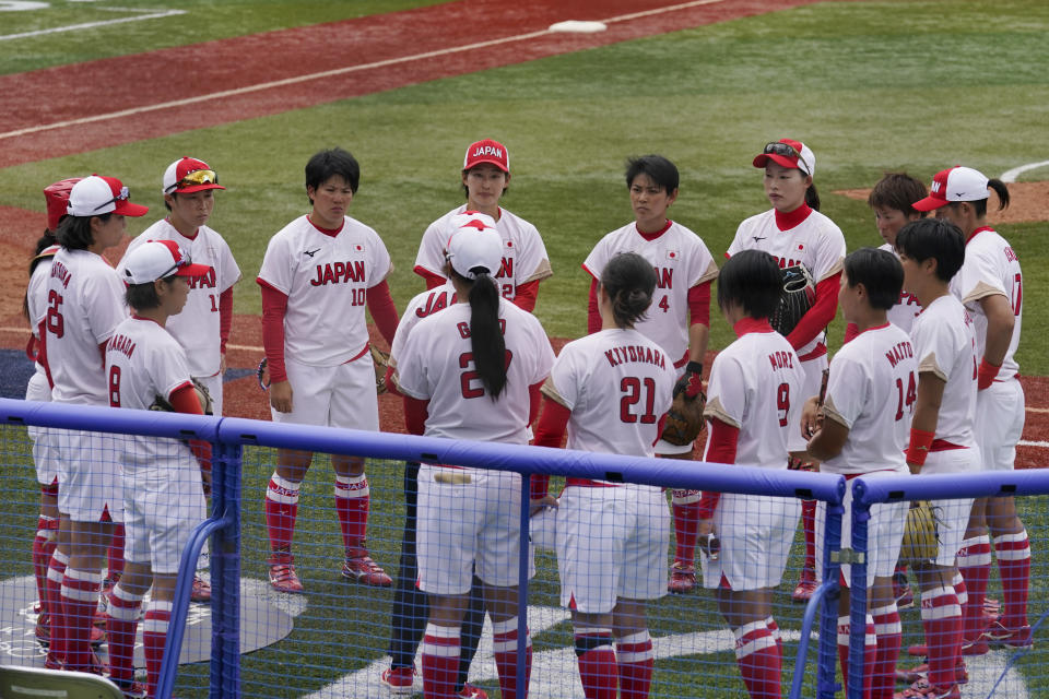 The Japan team talks after a loss to the United States in a softball game at the 2020 Summer Olympics, Monday, July 26, 2021, in Yokohama, Japan. (AP Photo/Sue Ogrocki)