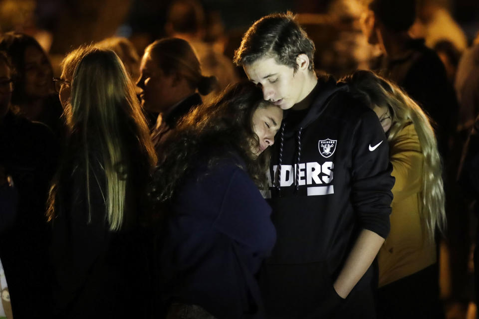 Hannah Schooping-Gutierrez, center, a student at Saugus High School, is comforted by her boyfriend Declan Sheridan, at right, a student at nearby Valencia High School during a vigil at Central Park in the aftermath of a shooting at Saugus Thursday, Nov. 14, 2019, in Santa Clarita, Calif. (AP Photo/Marcio Jose Sanchez)
