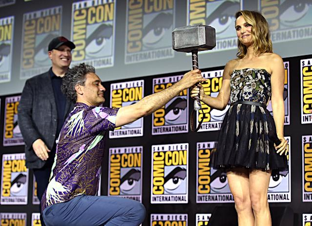 Marvel Studios boss Kevin Feige looks on as Taika Waititi present's Thor's hammer to Natalie Portman while announcing 'Thor: Love and Thunder' at San Diego Comic-Con International 2019. (Photo by Alberto E. Rodriguez/Getty Images for Disney)