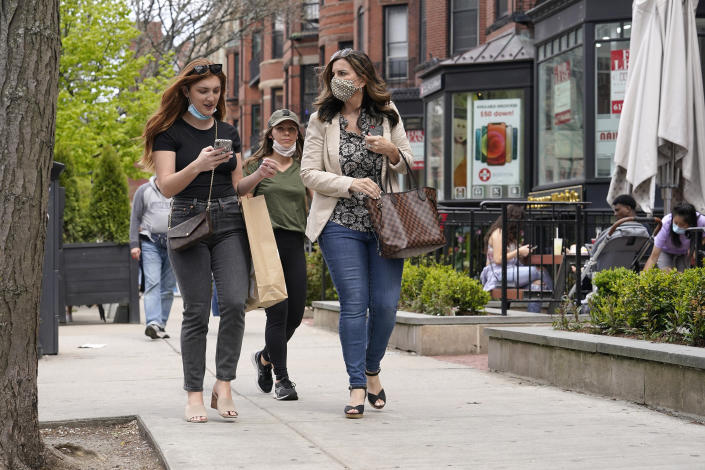 FILE - In this May 2, 2021, file photo, pedestrians walk along Boston's fashionable Newbury Street. COVID-19 deaths in the U.S. have tumbled to an average of just over 600 per day — the lowest level in 10 months — with the number of lives lost dropping to single digits in well over half the states and hitting zero on some days. (AP Photo/Steven Senne, File)