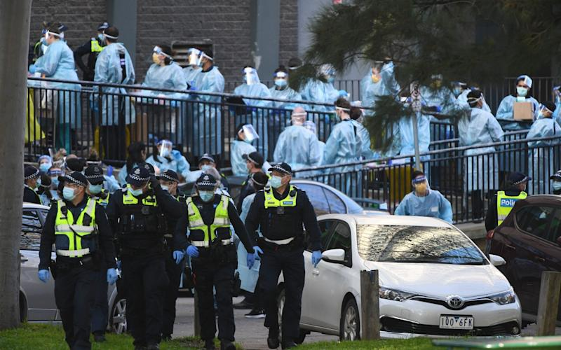 Victoria Police officers and healthcare workers congregate outside a public housing tower in North Melbourne, Australia - JAMES ROSS/EPA-EFE/Shutterstock