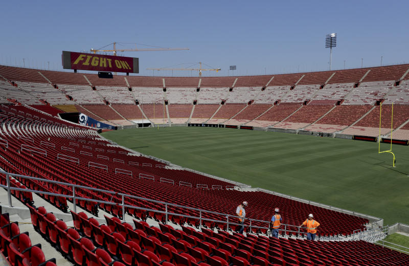 Stadium personnel walk near a new section of seats at the Los Angeles Memorial Coliseum in Los Angeles, Wednesday, Aug. 15, 2018. The 95-year-old Coliseum is only about halfway through its two-year, $300 million renovation project, the Rams and the Trojans have football games to play. The stadium that hosted two Olympics and the first Super Bowl will be open to the public again this weekend with new amenities in the famed concrete bowl. (AP Photo/Chris Carlson)