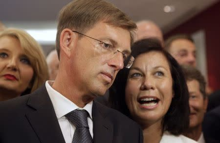 Miro Cerar, leader of the Stranka Mira Cerarja (Party of Miro Cerar), listens to his partner Vesna Arnsek (R) after he seeing preliminary results of elections in Ljubljana July 13, 2014. REUTERS/Srdjan Zivulovic