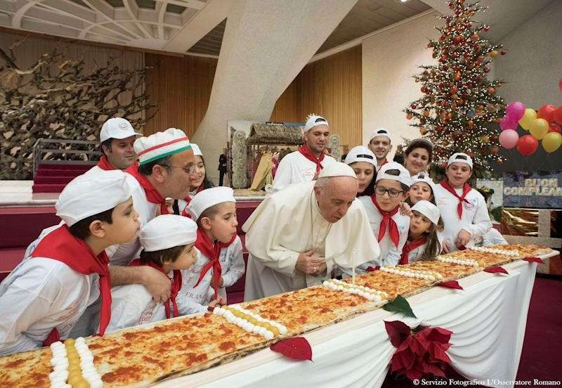 Pope Francis blows on a candleto celebrate his birthday during a special meeting at Paul VI hall at the Vatican on Dec.17, 2017.