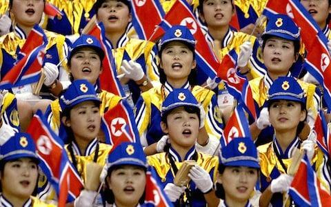 """The inclusion of an all-singing, all-dancing Olympic cheerleading squad as a key element of the most significant diplomatic breakthrough on the Korean Peninsula in two years may at first seem like an odd choice for two countries who are still technically at war. But the role of cheerleaders, chosen on the basis of their beauty and loyalty to the regime, has in the past been an important political tool for North Korea as it seeks to manipulate its image to the outside world during major sports events. North Korean women cheer their men's basketball team during a game against the Philippines at the 14th Asian Games in Pusan, September 30 , 2002. Their beauty, talent and graceful manners have made North Korea's official cheerleaders very popular in South Korea Credit: REUTERS The presence of a cheering squad in a high level North Korean delegation to Pyeongchang Winter Olympics in South Korea in February, was announced on Tuesday during the first talks between the countries since December 2015. Aware of the propaganda value of the regime's most attractive women performing choreographed moves in the stadiums, North Korea's state-controlled media has in the past crowed about southerners being captivated by the """"squads of beauty."""" North Korean cheerleaders show their support to their team before the quarter-final match against Germany in the FIFA Women's Football World Cup in Wuhan, in China's central province of Hubei, 22 September 2007 Credit: AFP In a sign of the high esteem placed on the job, Ri Sol-ju, now the wife of North Korea's leader Kim Jong-un was reportedly a member of a 101-strong cheerleading squad at the 2005 Asian Athletics Championships in Incheon, South Korea, when she was just 16. Typically cheerleaders have been about 20 years old, and selected from a good family background, although not generally from high-ranking families, and are often plucked from among university or music school students. The tradition began in 2002 during the Asian Games in Busa"""