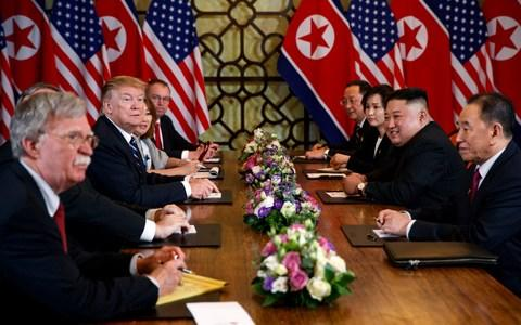 President Donald Trump speaks during a meeting with North Korean leader Kim Jong Un Thursday, Feb. 28, 2019, in Hanoi. At front right is Kim Yong Chol, a North Korean senior ruling party official and former intelligence chief. At left is national security adviser John Bolton. - Credit: AP