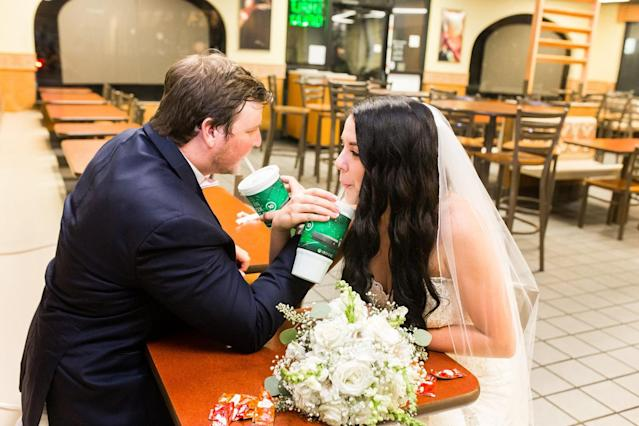 The newlyweds sipping sodas at Taco Bell. (Photo: Nikki B Photography)