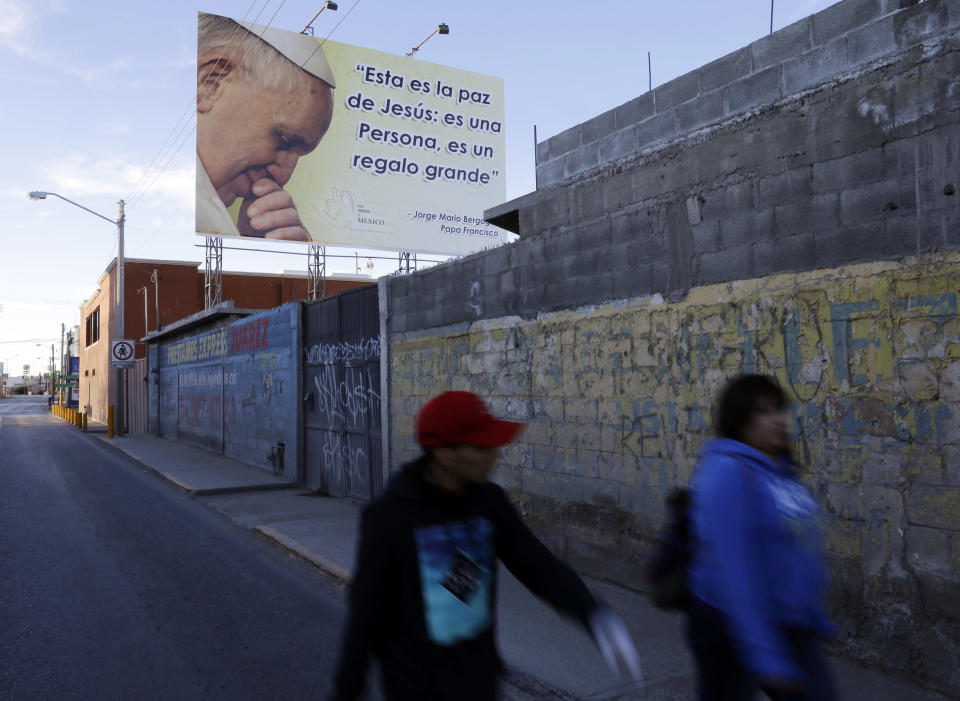 """FILE - In this Feb. 17, 2016, file photo, people pass an image of Pope Francis on their way to a route where he is scheduled to pass in Cuidad Juarez, Mexico. The sign displays a quote in Spanish by Pope Francis that reads: """"This is the peace of Jesus: he's a person, it's a big gift."""" (AP Photo/Gregory Bull, File)"""