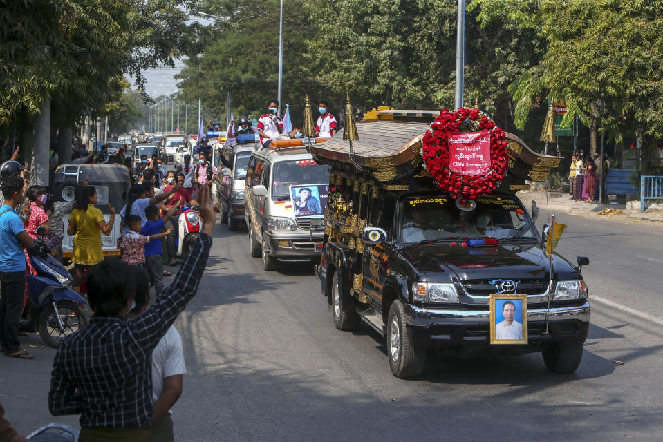 People flash the three-fingered salute as motorcade caring the coffin of Thet Naing Win is driven past in Mandalay, Myanmar, Tuesday, Feb. 23, 2021. Thet Naing Win was shot and killed by Myanmar security forces during an anti-coup protest on Saturday. (AP Photo)