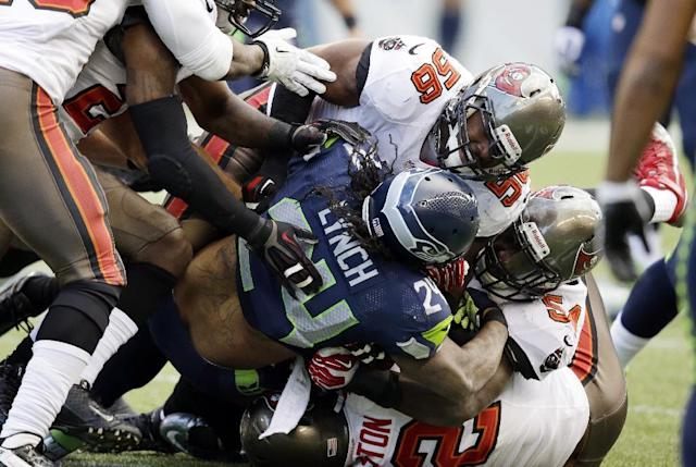 Seattle Seahawks running back Marshawn Lynch (24) is tackled by Tampa Bay Buccaneers' Dekoda Watson (56) during the second half of an NFL football game Sunday, Nov. 3, 2013, in Seattle. (AP Photo/Elaine Thompson)
