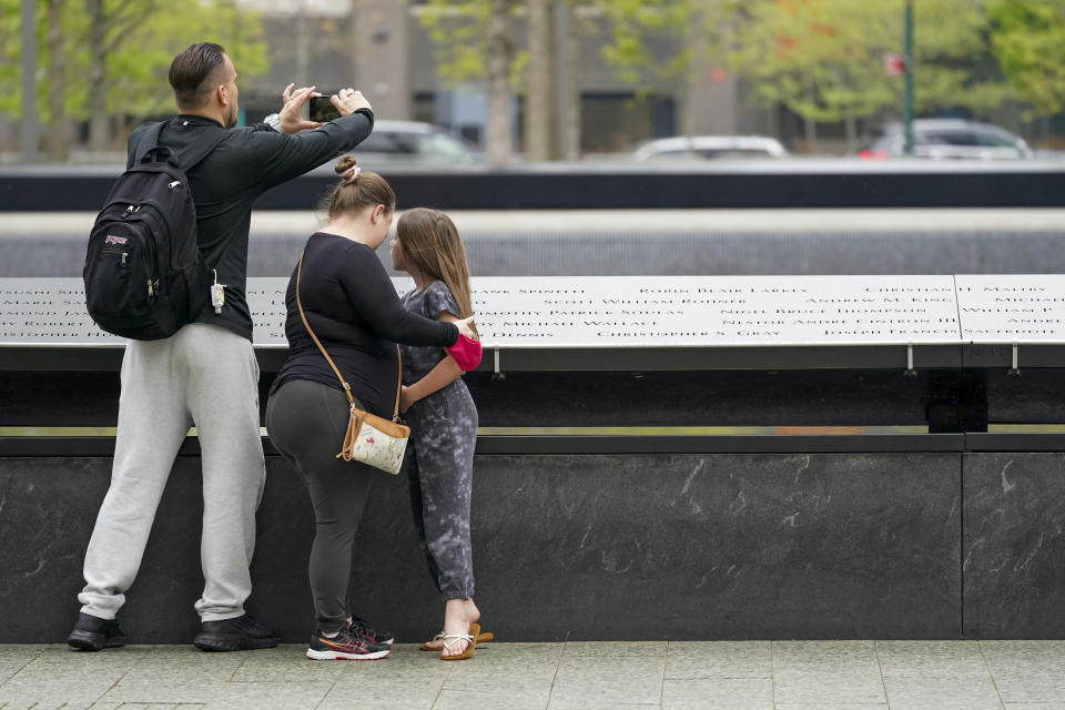 Visitors to the 9/11 Memorial and Museum take in the view of the North Pool, Thursday, April 29, 2021, in New York. In recent weeks, tourism indicators for New York City like hotel occupancy and museum attendance that had fallen off a pandemic cliff have ticked up slightly. It's a welcome sight for a city where the industry has been decimated by the impact of the coronavirus. (AP Photo/Mary Altaffer)