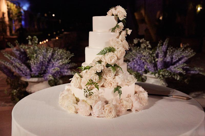 After dinner, guests regrouped in the square where the ceremony had taken place to watch the bride and groom cut their four-layer cake covered in white roses by Wedding Cakes in Tuscany.
