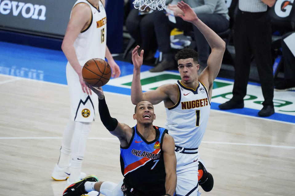 Oklahoma City Thunder forward Darius Bazley (7) is fouled by Denver Nuggets forward Michael Porter Jr. during the first half of an NBA basketball game Saturday, Feb. 27, 2021, in Oklahoma City. (AP Photo/Sue Ogrocki)
