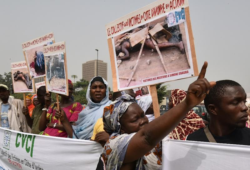 Relatives of victims of the 2010-2011 post-electoral crisis in Ivory Coast protest with pictures of the slain victims on January 13, 2015 in front of the Palace of Justice in Abidjan seeking sentencing for former first lady Simone Gbagbo (AFP Photo/Sia Kambou)