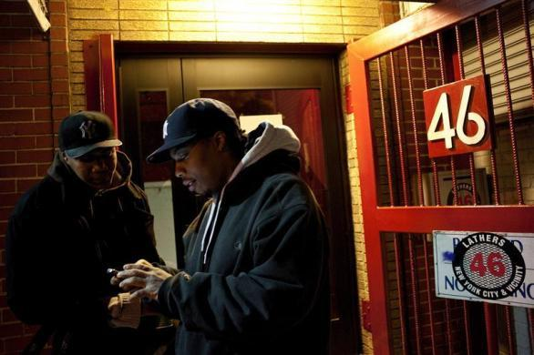 Job seekers look at text messages as they wait in front of the training offices of Local Union 46, a union representing metallic lathers and reinforcing ironworkers, in the Queens borough of New York, April 30, 2012.