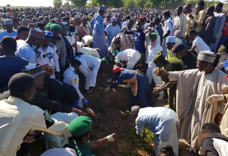 Men gather during the mass burial of people who were killed by militant attack, in Zabarmari