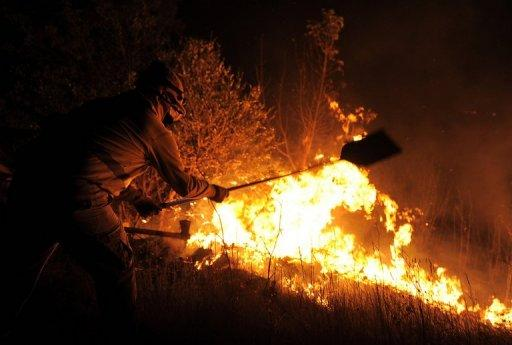 A firefigher tries to extinguish a wildfire in Ller near La Junquera (Girona), close to the Spanish-French border. The wildfire whipped up by strong winds left three people dead Sunday and about 100 people injured and forced thousands of residents to remain indoors, officials said