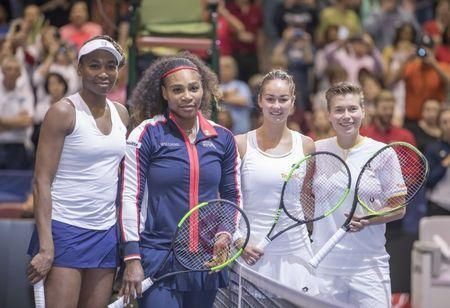 Feb 11, 2018; Asheville, NC, USA; Venus Williams (USA) and Serena Williams (USA) pose at the net with Lesley Kerkhove (NED) and Demi Schuurs (NED) before their Fed Cup match against Venus Williams (USA) at U.S. Cellular Center. Susan Mullane-USA TODAY Sports