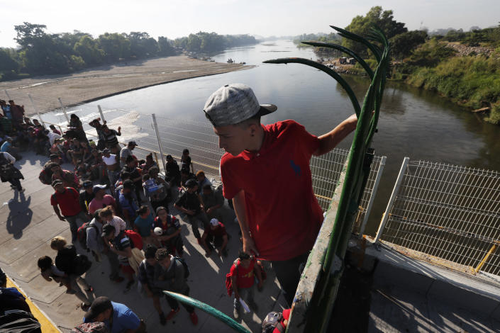 A migrant climbs the fence at the border crossing between Guatemala and Mexico in Tecun Uman, Guatemala, Saturday, Jan. 18, 2020. More than a thousand Central American migrants surged onto the bridge spanning the Suchiate River, that marks the border between both countries, as Mexican National Guardsmen attempted to impede their journey north. (AP Photo/Marco Ugarte)