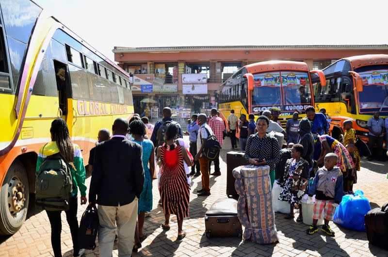 Passengers gather to board public transport buses as residents leave for the villages amid concerns over the spread of coronavirus disease (COVID-19) at a bus terminal in Old Kampala